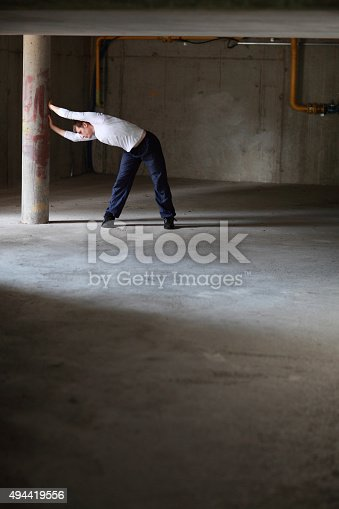 511849865 istock photo fit man stretching on dark parking lot 494419556