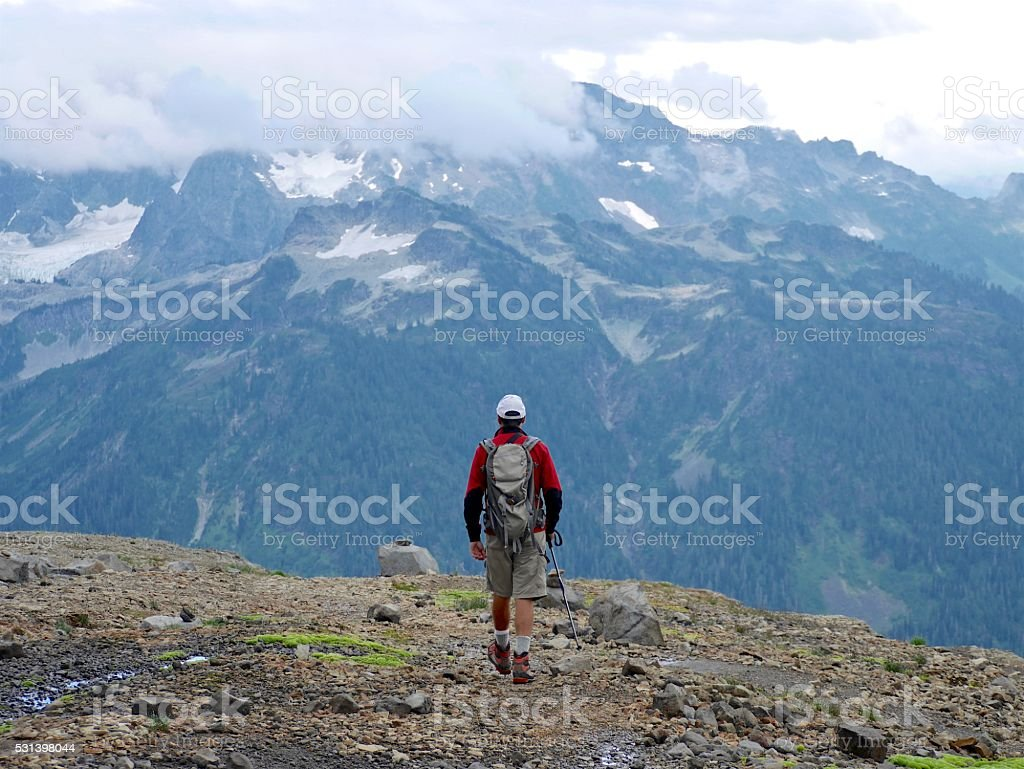 Fit Man with Backpack Walking on Mountains. stock photo