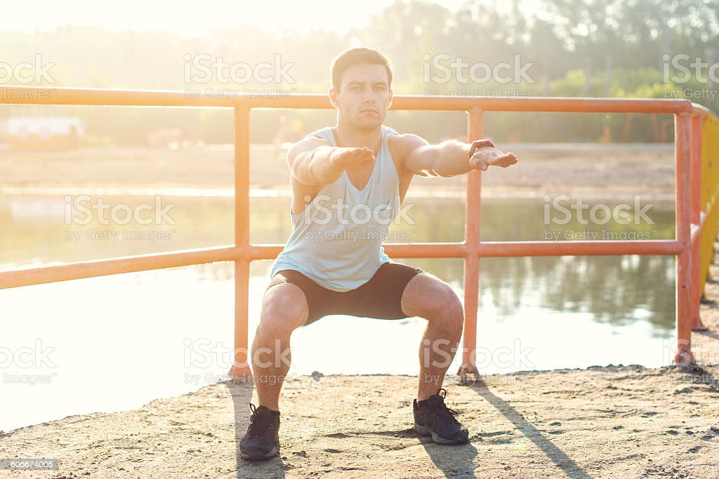 Fit man working out glutes with bodyweight workout doing squat stock photo