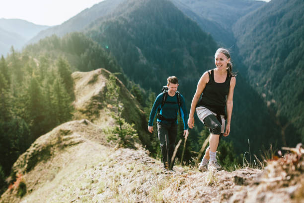 fit mature couple on mountain hike - hiking stock photos and pictures