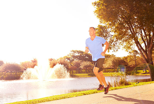 Fit Mature Male Athlete Running On Sidewalk stock photo