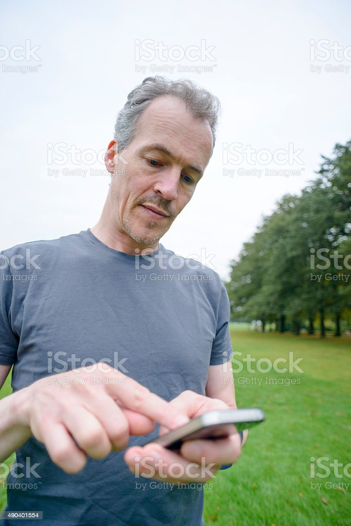 Fit Mature Man in Park Using Activity Tracker and Smartphone royalty-free stock photo