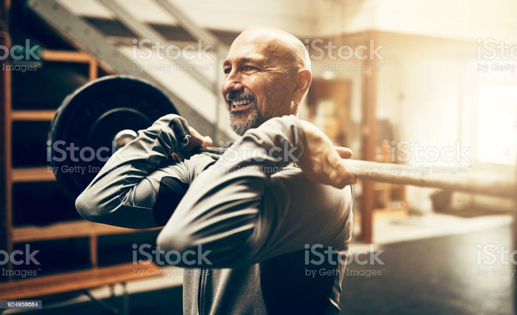 Hombre maduro forma levantar pesas y sonriendo en un gimnasio - foto de stock