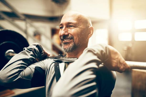 Hombre maduro sonriendo y levantando pesas en un gimnasio de forma - foto de stock