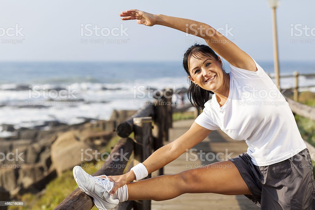 fit mature woman doing morning stretching stock photo