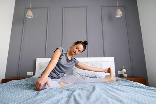 朝早くに彼女のベッドで彼女の足を伸ばす中年女性に合います穏やかで幸せを探しています - 1人のストックフォトや画像を多数ご用意