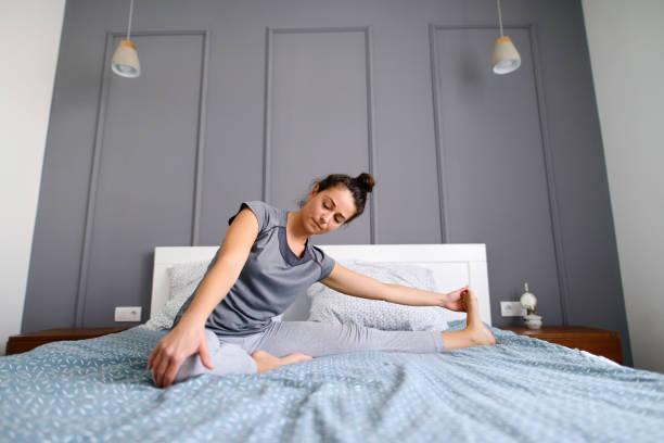 朝早くに彼女のベッドで彼女の足を伸ばす中年女性に合います。穏やかで幸せを探しています。 - ストレッチ ストックフォトと画像