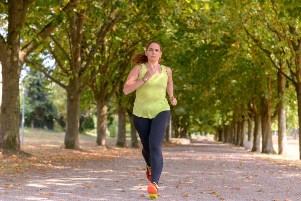 Fit middle-aged woman jogging through a park Fit middle-aged woman jogging along a tree-lined avenue through a park approaching the camera in a health and fitness or active lifestyle concept approaching stock pictures, royalty-free photos & images