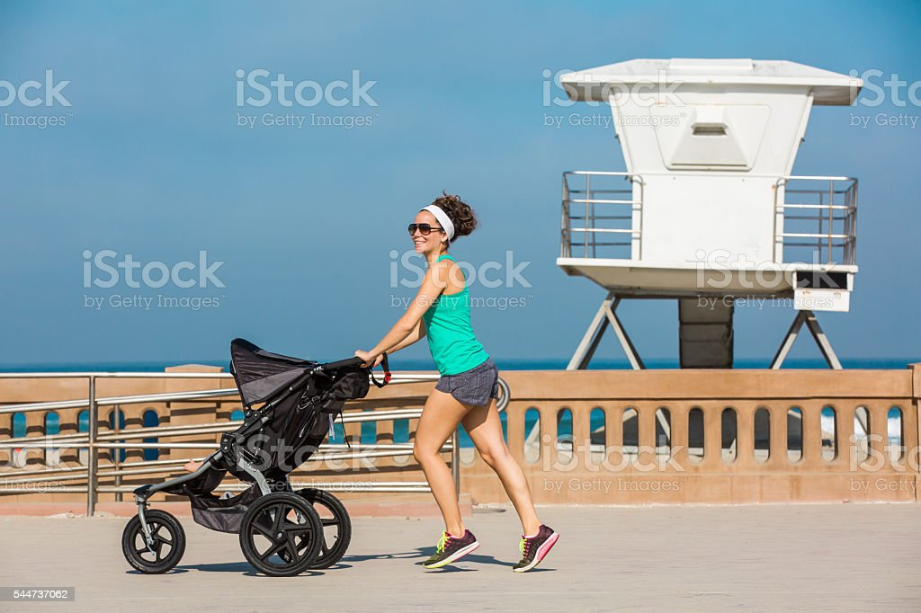 Fit Mom Running at the Beach with Baby Jogger - Royalty-free Baby - Human Age Stock Photo