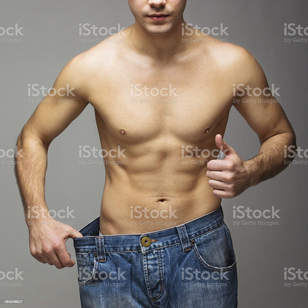 Fit muscular man in jeans after losing weight stock photo