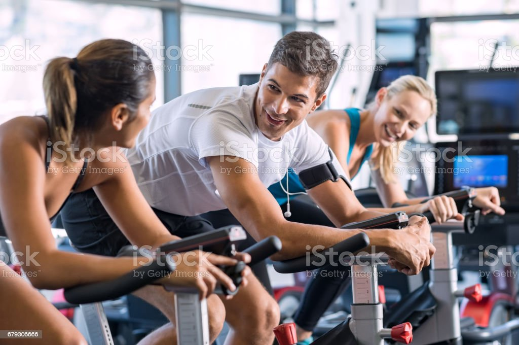 Fit people cycling at gym stock photo