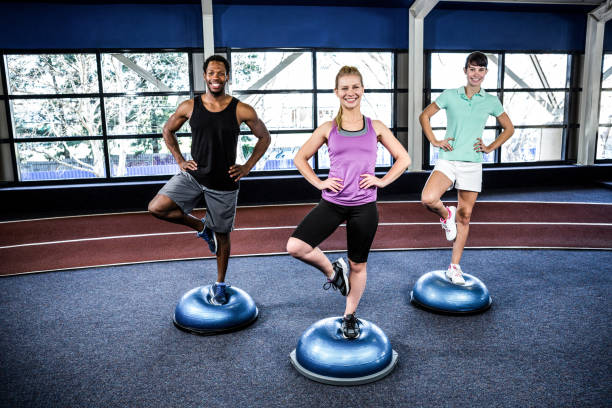 Fit people doing exercise with bosu ball stock photo