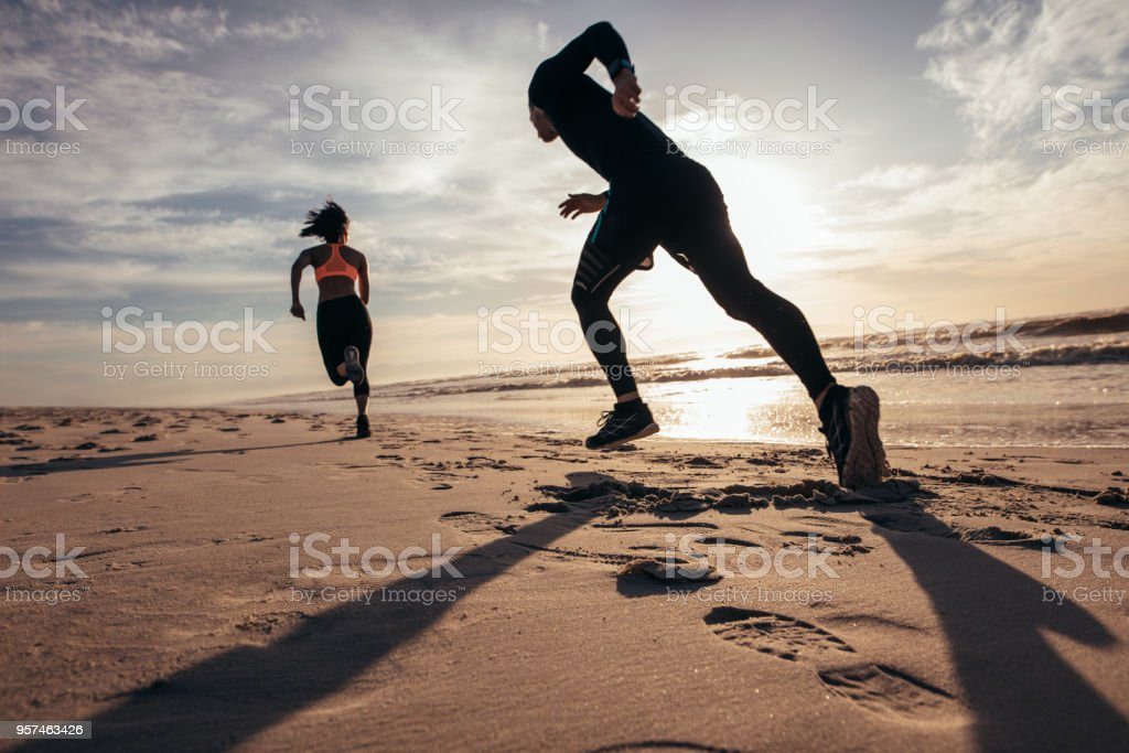 Fit people sprinting on the beach royalty-free stock photo