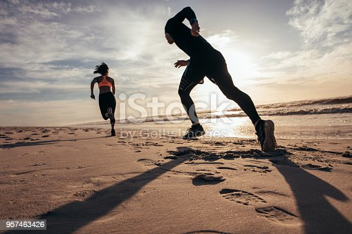 istock Fit people sprinting on the beach 957463426