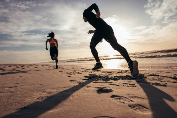 Fit people sprinting on the beach stock photo