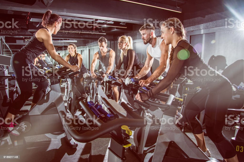 Fit people working out at spinning class in the gym. stock photo