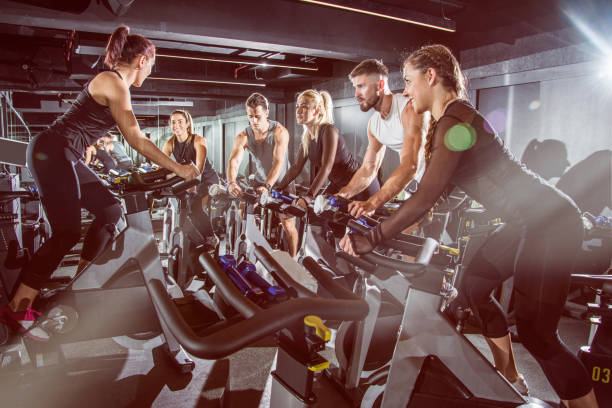 Fit people working out at exercising class in the gym. Fit people working out at exercising class in the gym. exercise bike stock pictures, royalty-free photos & images