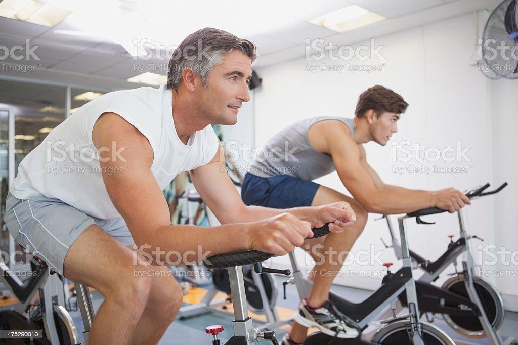 Forma personas que trabajan en la sala de bicicletas fijas - foto de stock