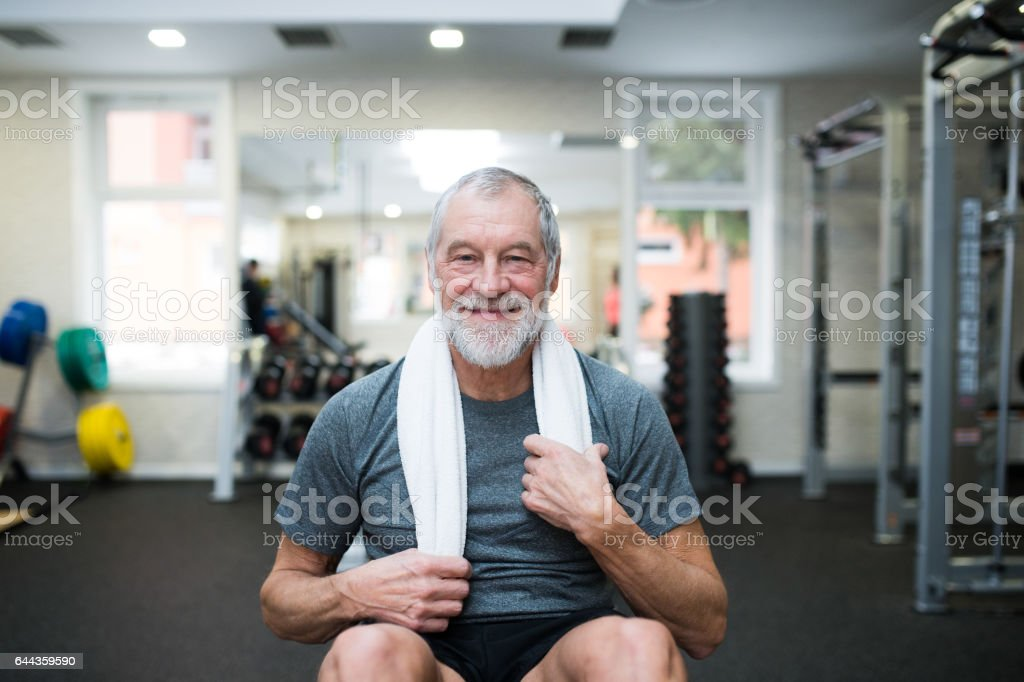 Fit senior man in gym working his abs, doing crunches. stock photo
