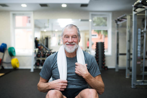 Fit senior man in gym working his abs, doing crunches. Fit senior man in gym in sports clothing working his abs, doing abdominal crunches. one senior man only stock pictures, royalty-free photos & images