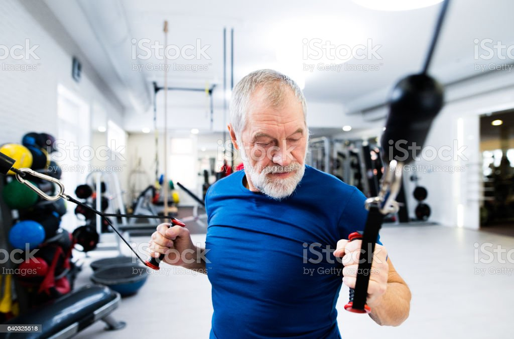 Fit senior man in gym working out with weights. - foto stock