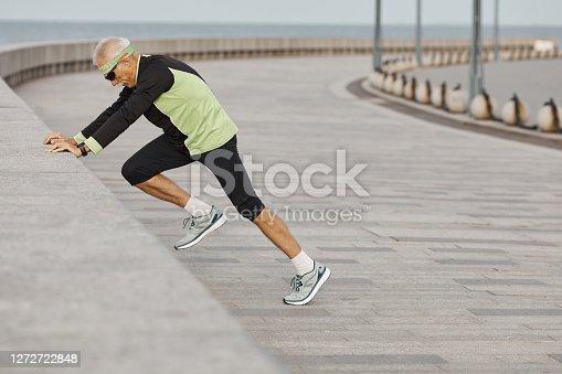 Horizontal side view shot of sporty senior man doing morning aerobic exercises outdoors