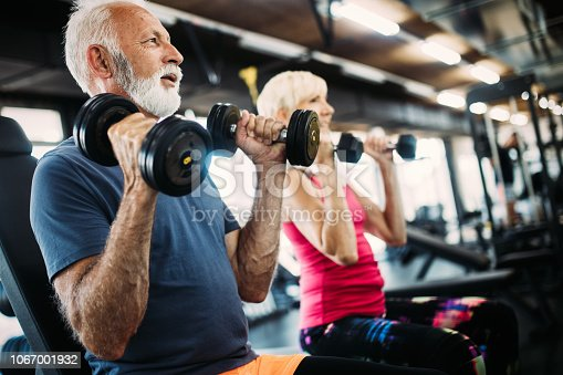 istock Fit senior sporty couple working out together at gym 1067001932