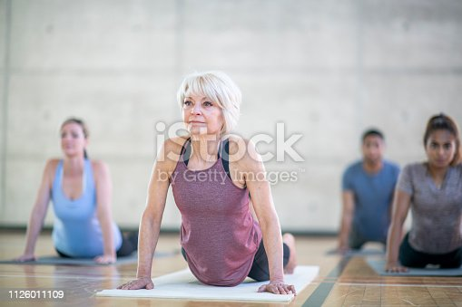 A very diverse group of friends workout one day together. A senior woman looks off into the distance while holding a stretch.