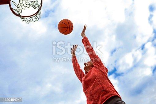 Fit woman playing basketball