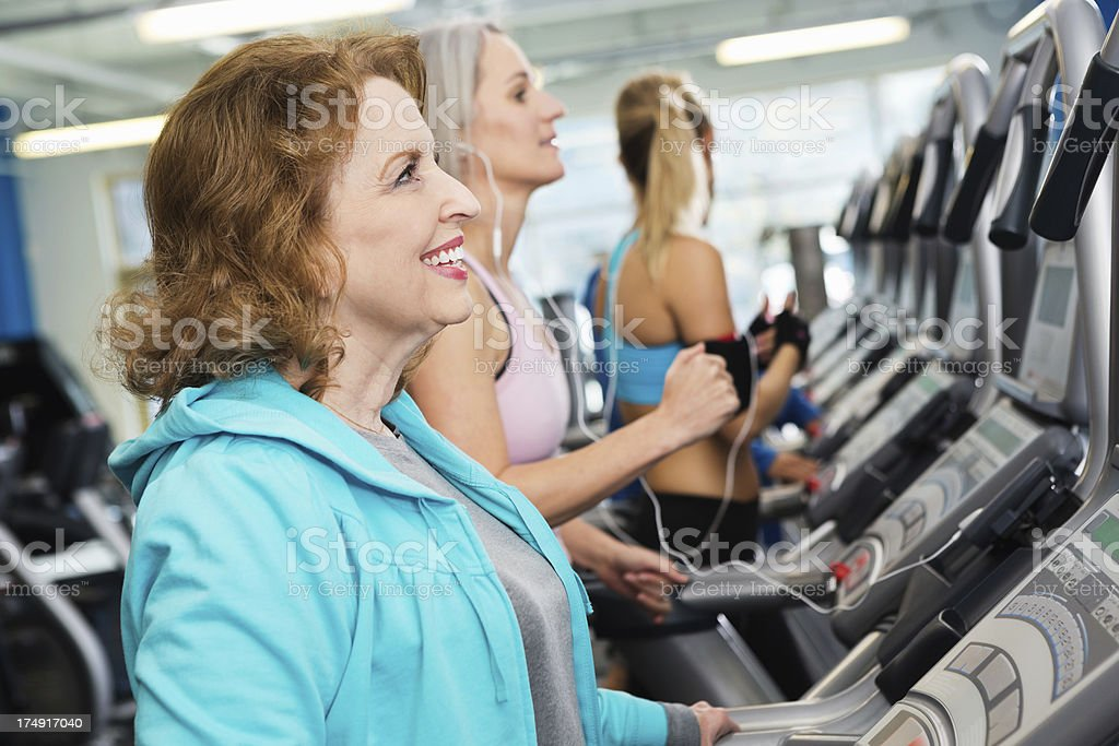 Fit senior woman working out on treadmill in crowded gym stock photo