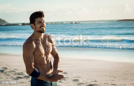 519676858istockphoto fit smiling man relaxing on the beach 519676636