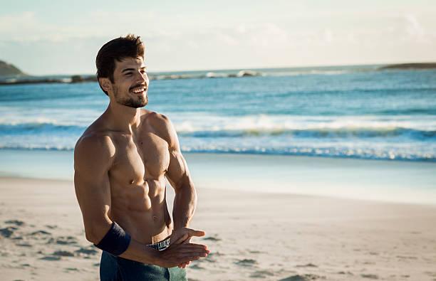 vestibilità uomo sorridente rilassante sulla spiaggia - man city exercise abs foto e immagini stock