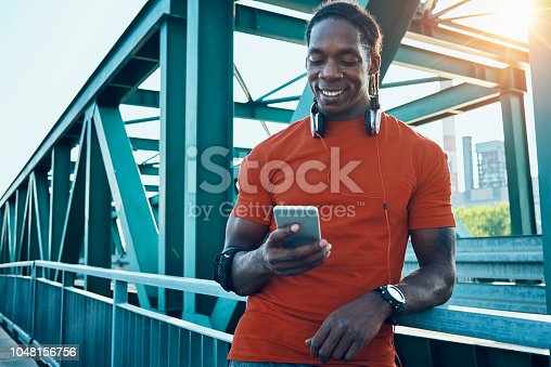athletic man taking a break and using his smartphone