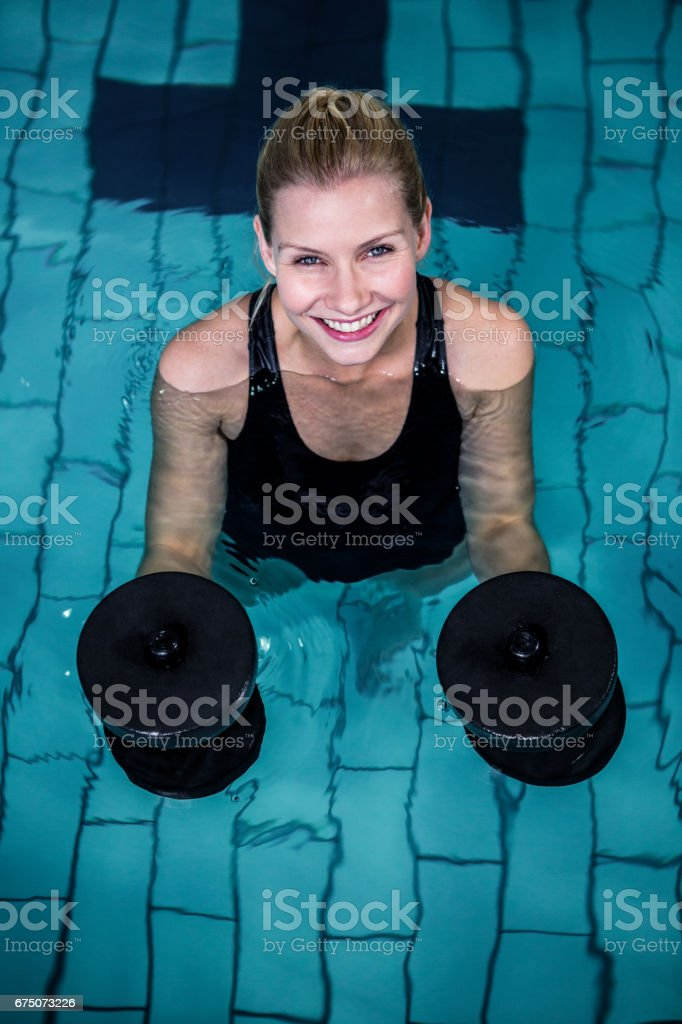 Fit smiling woman holding weights - foto stock