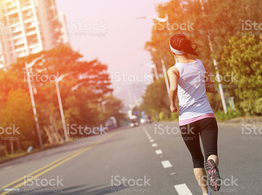 fit sports woman running at asphalt road back of healthy sports woman running at asphalt road Active Lifestyle Stock Photo