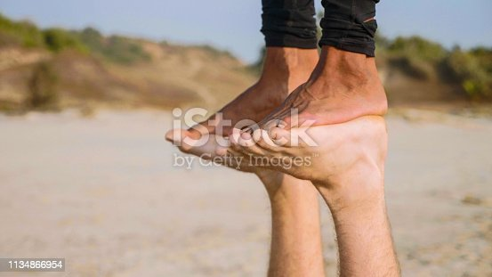 istock Fit sporty couple practicing acro yoga with partner together on the sandy beach. 1134866954