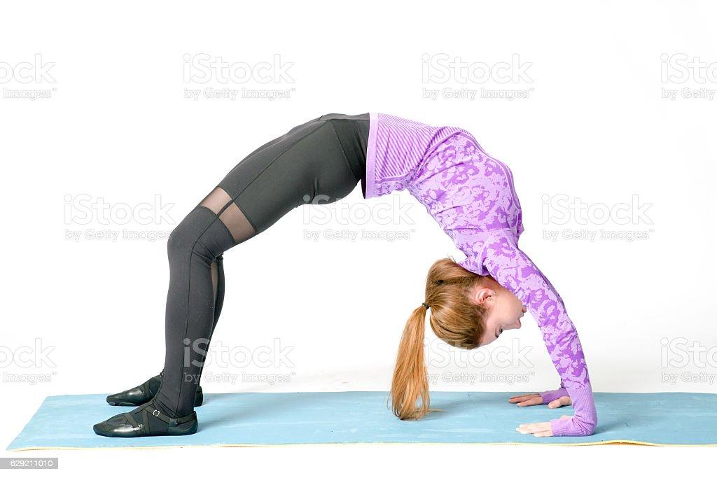 Fit sporty girl doing backbend exercise. Camatkarasana, stock photo