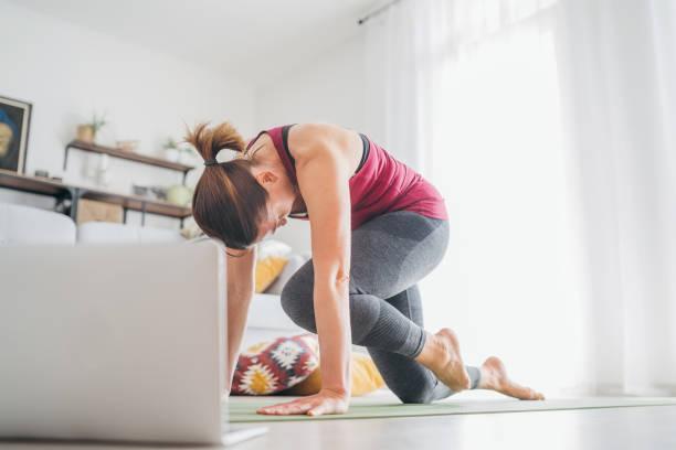 Ajuste a la mujer causasiana saludable deportiva en la estera en una pose de yoga, haciendo ejercicios de respiración, viendo la clase de yoga en línea en la computadora portátil. Personas sanas y concepto de automotivación. - foto de stock