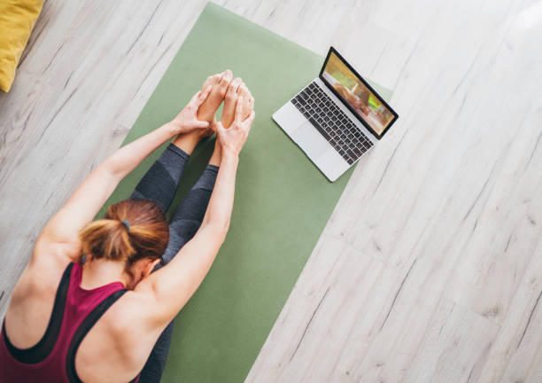 Ajuste mujer deportiva y saludable sentada en la alfombra en Paschimottanasana pose, haciendo ejercicios de respiración, viendo la clase de yoga en línea en la computadora portátil. Personas sanas y automotivación Concepto de vista superior. - foto de stock