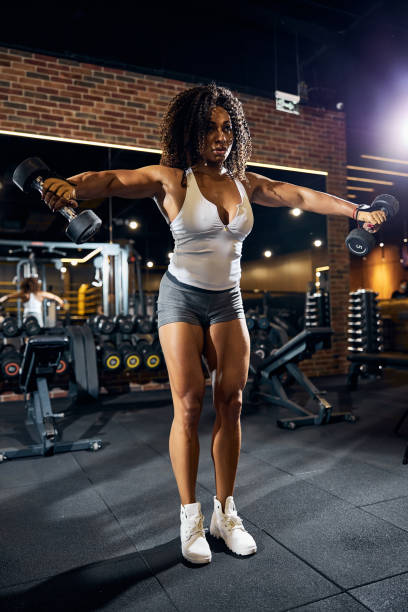 Fit sporty lady exercising with hand weights Full-sized portrait of a sportswoman performing the standing lateral raises with a pair of dumbbells lateral surface stock pictures, royalty-free photos & images