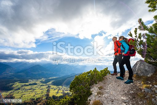 hiking fit mountaineers couple woman man 45 yeras old standing on gravel path in mountains enjoying beautiful view over valley on sunny autumn day