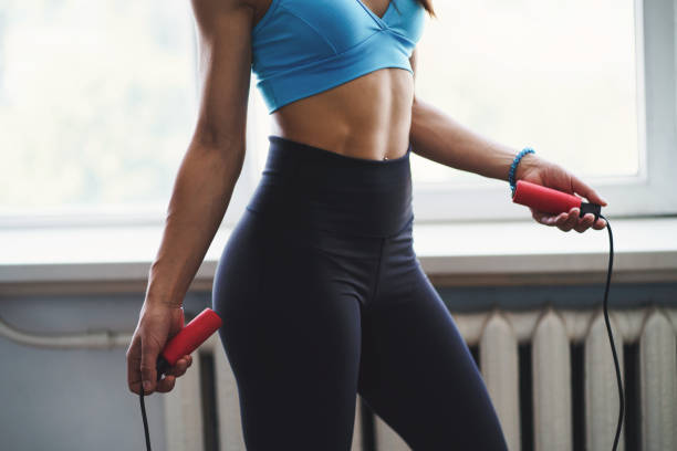 Fit sporty woman begin training with jumping rope stock photo