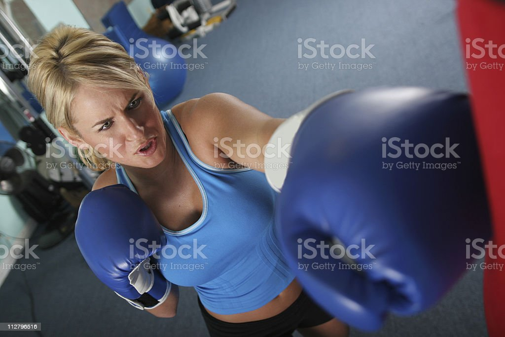 fit sporty woman puncking a boxing bax exercising in gym royalty-free stock photo