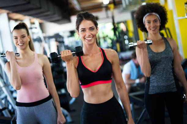 Fit sporty women exercising and training at fitness club stock photo