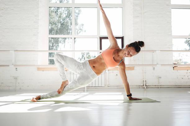 Fit starke Frau erstreckt sich auf Yoga-Matte in weißen Turnhalle sitzen zu tun. Sportliche Frau Training am frühen Morgen – Foto