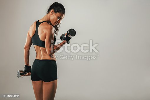 istock Fit strong young woman lifting weights 621586122