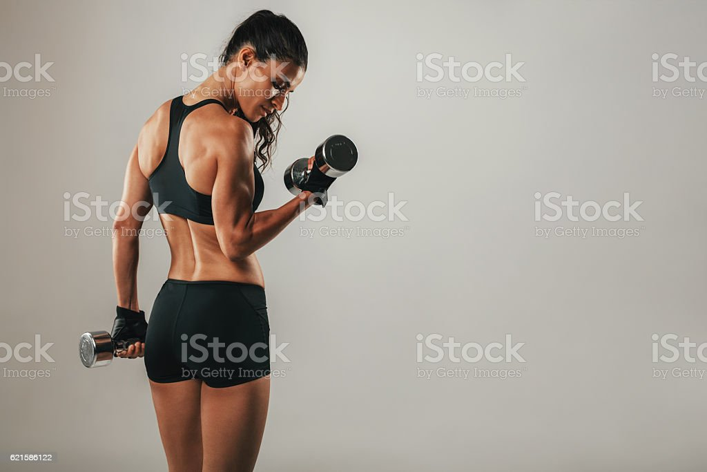 Fit strong young woman lifting weights stock photo