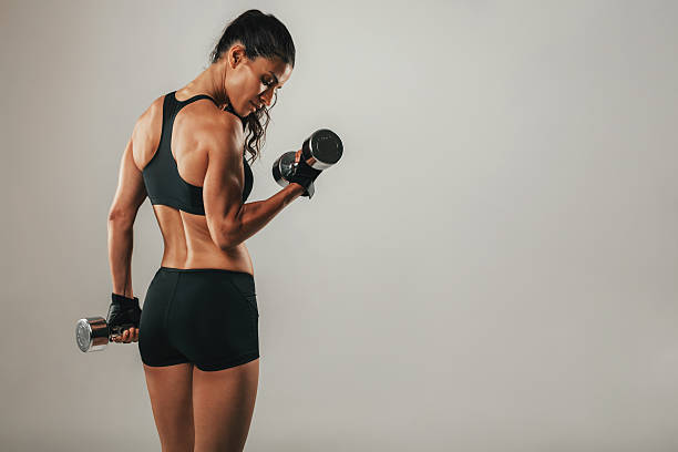fit strong young woman lifting weights - weights stock photos and pictures