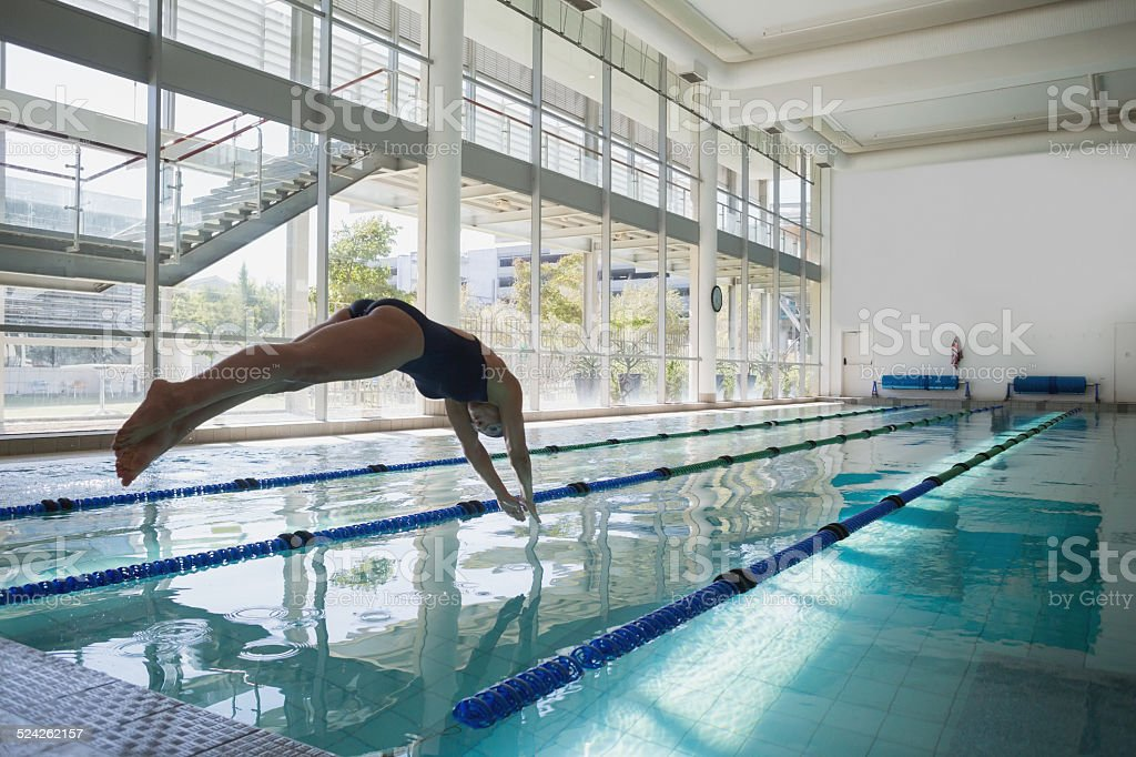 Fit swimmer diving into the pool at leisure center stock photo