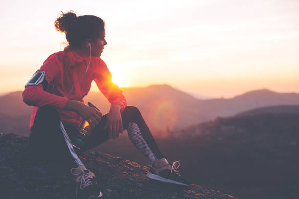Fit woman athlete resting outdoors Athletic woman resting after a hard training in the mountains at sunset. Sport tight clothes. leisure equipment stock pictures, royalty-free photos & images